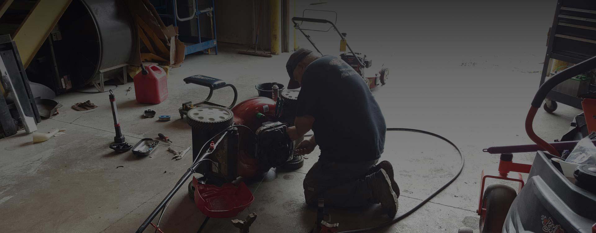 man repairing a lawn mower